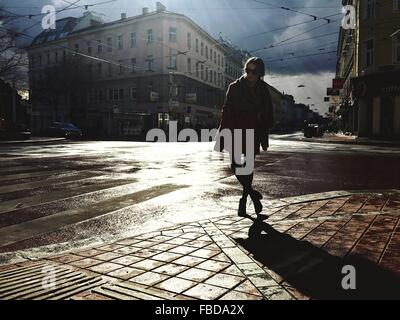 Woman Standing On Wet Street In City - Stock Photo
