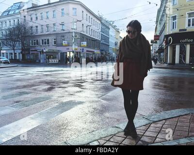 Young Woman Standing On Wet Street In City - Stock Photo