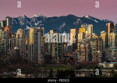 Downtown skyline with snowy mountains behind at dusk, Vancouver, British Columbia, Canada - Stock Photo