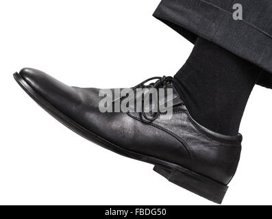 side view of male left leg in black shoe takes a step isolated on white background - Stock Photo