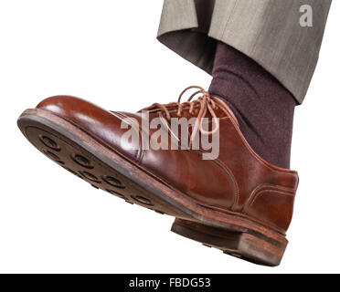 male left foot in brown shoe takes a step isolated on white background - Stock Photo