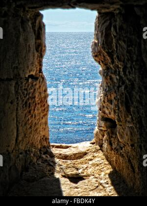 Window In Stone Wall Overlooking Calm Sea - Stock Photo