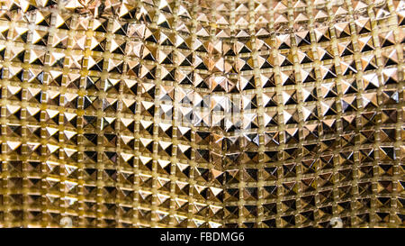Background formed by a coating of little golden pyramids.