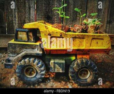 Close-Up Of Messy Toy Truck Against Wooden Fence - Stock Photo