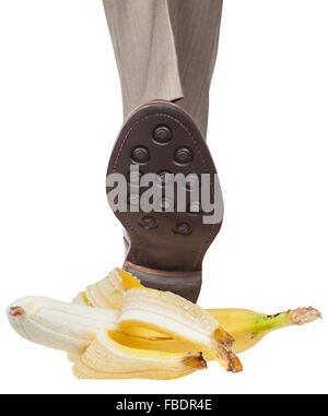 male leg in the left brown shoe stepping on banana peel isolated on white background - Stock Photo