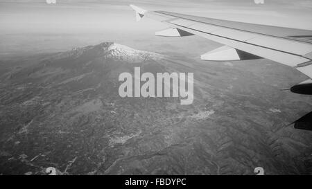 Cropped Image Of Airplane Flying Above Snow Covered Mount Etna - Stock Photo