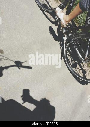 Low Section Of Person Riding Bicycle On Street - Stock Photo