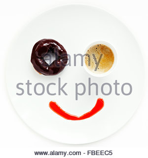 Smiling face made of donut and cup of coffee on the plate - Stock Photo