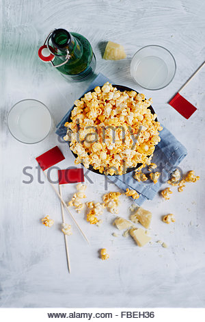 Bowl of popcorn on white rustic background with two glass of drink and green bottle - Stock Photo