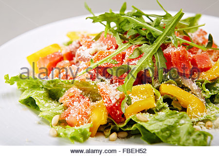 Stylised healthy salad with mixed greens, smoked salmon, tomatoes and paprica. Lots of copyspace - Stock Photo