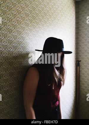 Side View Of Woman In Hat Standing Against Wall While Looking Down - Stock Photo