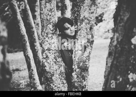 Young Man Standing Behind Tree Trunks In Park - Stock Photo