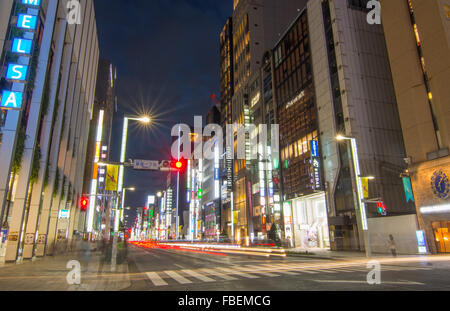 Tokyo Japan local crowds Ginza shopping twilight traffic blurs of movement on street downtown with rush of locals - Stock Photo