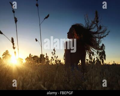 Silhouette Woman Sitting On Grassy Field Against Clear Sky During Sunset - Stock Photo