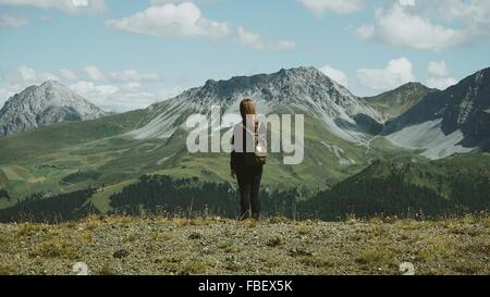 Rear View Of Woman Hiking On Mountains - Stock Photo