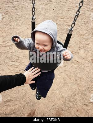 Cropped Image Of Parent Pushing Baby Boy In Swing At Park - Stock Photo