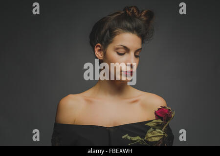 Beautiful Young Fashion Model Looking At Red Rose Against Gray Background - Stock Photo