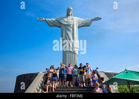 Tourists posing in front of famous Christ the Redeemer statue atop the Corcovado mountain in Rio de Janeiro, Brazil. - Stock Photo