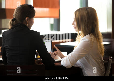 Two young caucasian office women meeting, discussing business, sitting at the table, beside laptop, rear view - Stock Photo