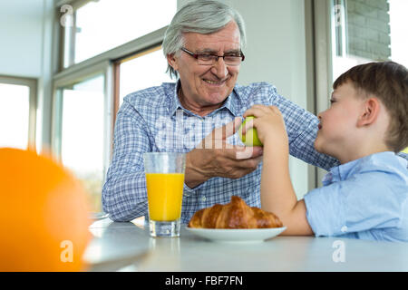 Grandfather and grandson having breakfast - Stock Photo