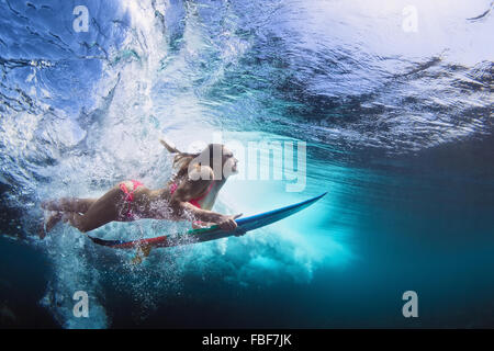 Young girl in bikini - surfer with surf board dive underwater with fun under big ocean wave. - Stock Photo