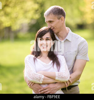 Couple of lovers on a date, young man tenderly cuddling with his happy smiling girlfriend, kissing her hair with - Stock Photo
