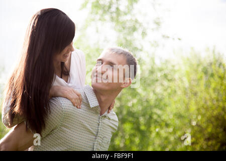 Couple in love on a date, young man giving his beautiful girlfriend piggyback ride, happy smiling, having fun together, - Stock Photo