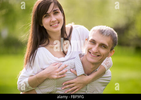 Portrait of happy couple in love on a date, young man giving his beautiful girlfriend piggyback ride, smiling, having - Stock Photo
