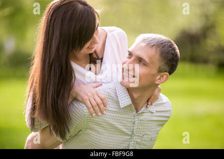 Portrait of happy young man and woman in love on a date, boyfriend giving his beautiful girlfriend playful piggyback - Stock Photo