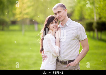 Portrait of happy couple, young man and woman on romantic date, hugging each other, girlfriend leaning on her boyfriend, - Stock Photo