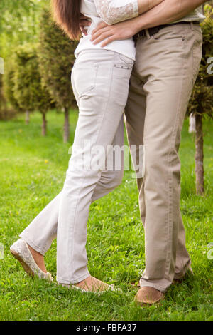 Couple in love, attractive young man and woman on romantic date in park, hugging each other, close up of legs - Stock Photo