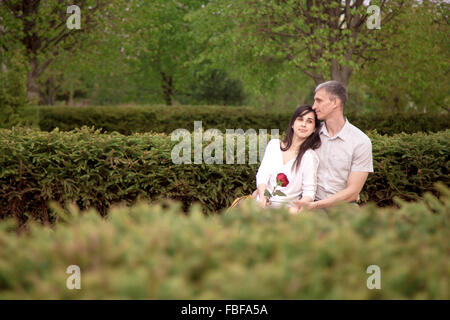 Couple of young lovers sitting close on wooden bench in park on a date with dreaming expressions, resting, copy - Stock Photo