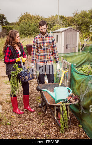 Couple with basket of vegetables and wheelbarrow - Stock Photo