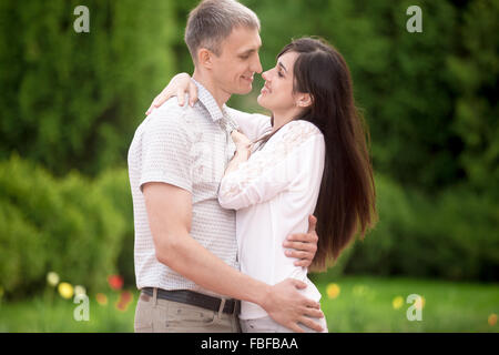Couple of lovers on a date in park, standing face to face, young man tenderly embracing his happy smiling girlfriend, - Stock Photo