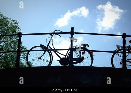 Low Angle View Of Bicycle Parked On Bridge Against Cloudy Sky - Stock Photo