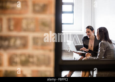 Businesswomen using laptop on the couch - Stock Photo