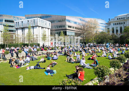 Office workers and tourists relaxing in the sunshine at Festival Gardens by St Paul's Cathedral, City of London, - Stock Photo