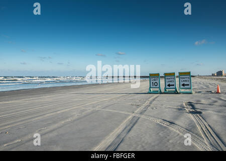 10 mph Speed Limit and Traffic Lane signs pointing left towards the ocean with left curving tire tracks on the beach - Stock Photo