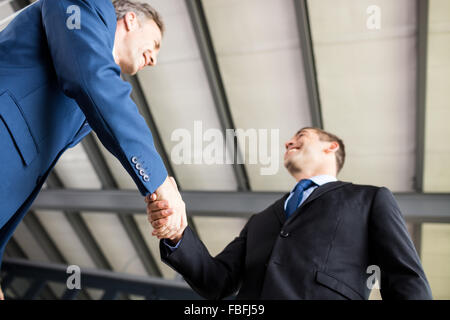 Two smiling businessmen shaking hands - Stock Photo