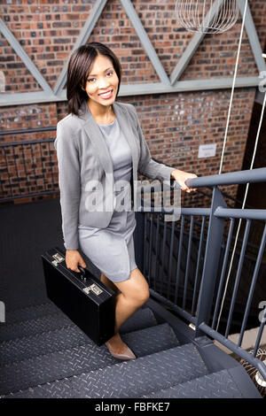 Smiling businesswoman climbing stairs with briefcase - Stock Photo