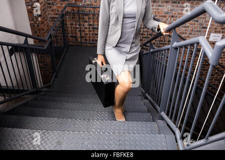 Businesswoman climbing stairs with briefcase - Stock Photo