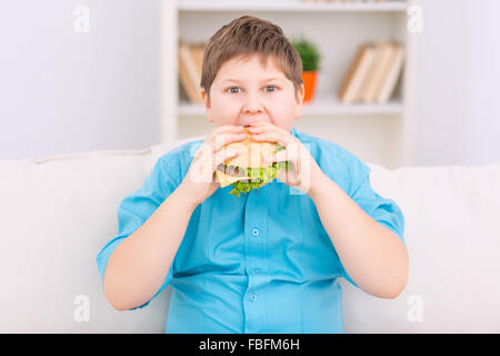 Chubby kid is eating a burger. - Stock Photo