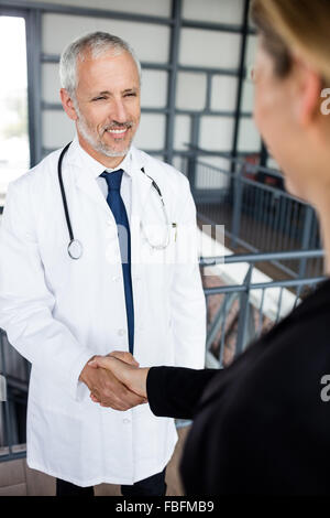 Businesswoman and doctor make a handshake - Stock Photo
