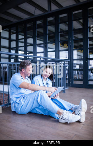 Smiling medical team working on floor - Stock Photo