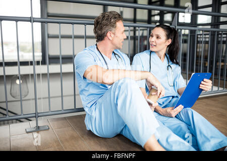 Medical team discussing the report on clipboard - Stock Photo