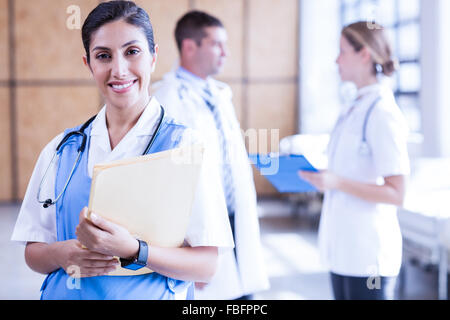 Smiling nurse holding report on clipboard - Stock Photo