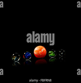 Five coloured, glass marbles on a reflective surface in front of a black background - Stock Photo