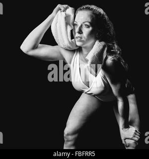 Composite image of athlete wiping sweat with towel while looking up - Stock Photo