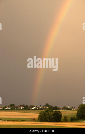 Rainbow in Bavaria after a summer thunderstorm. - Stock Photo