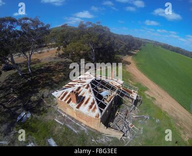 Aerial view of dilapidated historic cottage next to green wheat field, near Moora, Wheatbelt region, Western Australia - Stock Photo